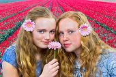 Two teenage girls in front of red tulips field