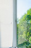 picture of louvers  - closed plastic blinds on the window with the reflection in the glass