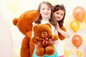 Pretty sisters posing with teddy bears in playroom
