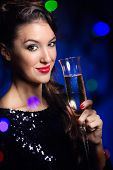 Beautiful girl in evening dress with wine glass. New Year's Eve.