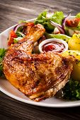 Barbecued chicken leg with boiled potatoes and vegetables