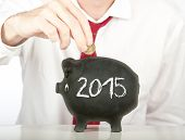 businessman putting money on a piggy bank with a year 2015 drawing
