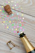 Overhead of a bottle of champagne with the cork popping on a rustic wood table. The spray from the bottle is made of colorful stars. With copy space it is perfect for New Years party and celebrations