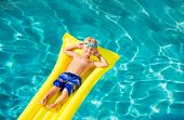 Young Boy Relaxing and Having Fun in Swimming Pool on Yellow Raft. Summer Vacation Fun. Relaxing Lifestyle Concept.