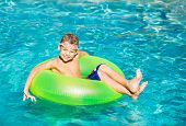 Young Kid Having Fun in the Swimming Pool On Inner Tube Raft. Summer Vacation Fun.