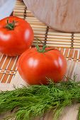 Red tomato on a table with dill
