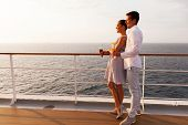 side view of smiling couple having cocktails on cruise ship at sunset
