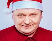 Close up portrait of evil aged man in Santa Claus hat and red shirt over white background