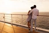 stock photo of married couple  - back view of young couple hugging at sunset on cruise ship - JPG