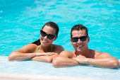 smiling young couple leaning on poolside