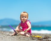 pic of shoulder-blade  - cute baby girl playing in the sand with a shovel on the beach - JPG