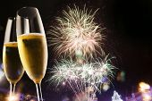 Toasting with champagne glasses against fireworks