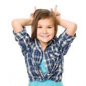 Portrait of a happy little girl laughing and making horns or bunny ears, isolated over white