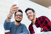 image of entrepreneur  - Outdoor portrait of two young entrepreneurs taking a selfie at coffee shop - JPG