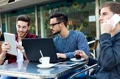 picture of entrepreneur  - Outdoor portrait of young entrepreneurs working at coffee bar - JPG