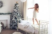 Preteen child girl wake up and jumping on her bed near decorated Christmas tree in beautiful hotel room in the holiday morning
