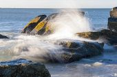 picture of dartmouth  - Water from breaking wave sheets off rock - JPG