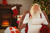 Relaxed santa writing list with a quill at home in the living room