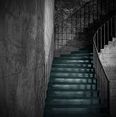 stock photo of spooky  - Spooky old stone interior staircase with rusty handrail - JPG