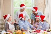 Happy extended family in santa hat speaking together at home in the living room