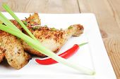 grilled meat : grilled quarter chicken garnished with green sweet peas , red peppers on white plates over wooden table
