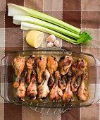 Grilled chicken drumsticks and vegetables in transparent pot