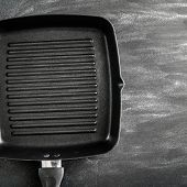 Cast iron griddle pan on black background