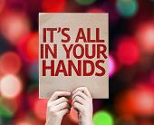 It's All In Your Hands card written on colorful background with defocused lights