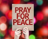 Pray For Peace card written on colorful background with defocused lights
