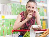 Woman Checking Receipt At Supermarket