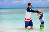 Father and son with snorkeling equipment fins and mask at tropical beach
