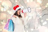 Festive brunette holding megaphone and bags against white glowing dots on grey