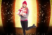 Festive blonde holding pile of gifts against glittering screen on black background