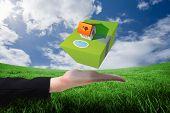 Businesswomans hand presenting against green field under blue sky
