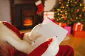 Santa claus writing list with a quill at home in the living room