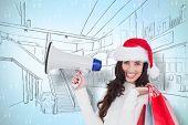 Smiling brunette holding gift bags and megaphone against green reindeer pattern