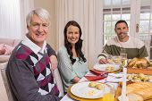 Cheerful family looking at camera during christmas dinner at home in the living room