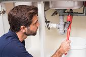 stock photo of plumber  - Plumber fixing under the sink in the kitchen - JPG