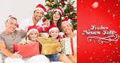 Happy family at christmas holding gifts against red vignette