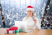 Festive blonde shopping online against glittering lights in room