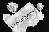 Crumpled Paper Sheet With Word Unemployment Isolated On Black