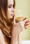 Beautiful girl standing at the window with a hot Cup of invigorating coffee early in the morning