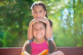 Happy Hispanic Sisters Reading Book In Summer Park