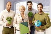 image of work crew  - Team portrait of environment friendly businesspeople holding green plants and globe - JPG