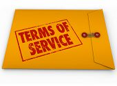 Terms of Service words on stamp on yellow envelope to illustrate a contract, obligations, agreement and restrictions in signing up for service or using software