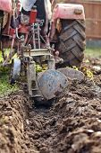 foto of plow  - Image from the back of a tractor plowing the land focus is on plow - JPG