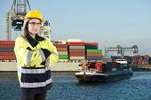 Female Shore Pilot looking into the camera whilst guiding an inland vessel to its mooring in a commercial harbor where a large container ship is being unloaded