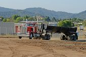 foto of dump_truck  - Dump truck at a large construction site removing a hill during an airport runway expansion project - JPG