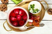 Traditional polish clear red borscht with dumplings and Christmas decorations on wooden background