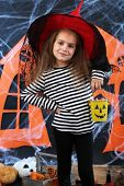 Little girl in hat with pail for candy on Halloween decorations background